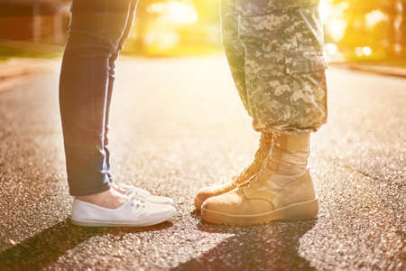 army boots: Young military couple kissing each other, homecoming concept, soft focus,warm orange toning applied Stock Photo