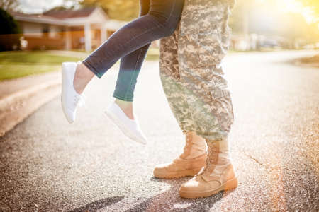 military uniform: Young military couple kissing each other, homecoming concept, warm orange toning applied