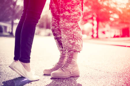 カップルがお互いにキス、ホームカミング概念、ソフト フォーカス、クロス プロセス調若い軍適用、光リークのコーナーで