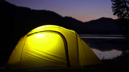 The yellow tent costs on the bank of the mountain lake. Night. In a tent light burns. Beautiful look.