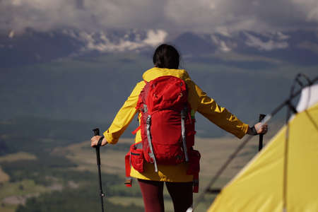 Young happy woman with backpack standing on a rock and looking to a valley below. On the cliff is a yellow tent. Banque d'images