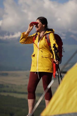 Young happy woman with backpack standing on a rock and looking through binocular to a valley below. On the cliff is a yellow tent.