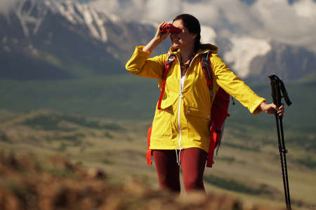 Young happy woman with backpack standing on a rock and looking through binocular to a valley below. Banque d'images