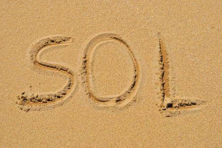 sunburnt: The sun word written in the sand of the beach.