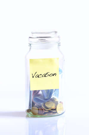 Glass jar with coins and word vacation. photo