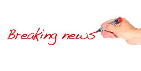 Hand writing the phrase Breaking news on white background  photo