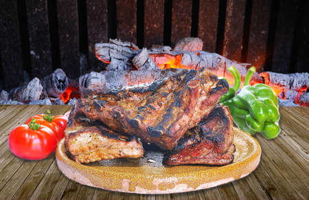 Pork ribs with and vegetables on barbecue table  photo