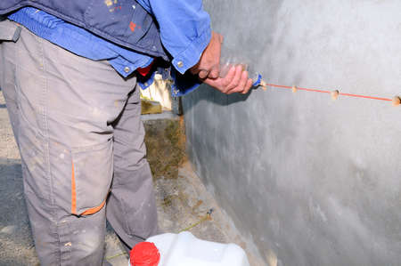 Construction worker waterproofing a wall