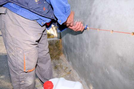 Operaio edile impermeabilizzazione di un muro