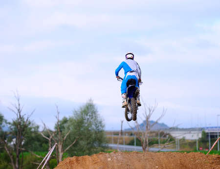 Motocross racer giving a jump with his bike  photo