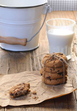 Homemade cookies with glass of milk on wooden table. photo