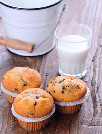 Cupcakes with glass of milk on wooden table. photo