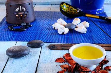hot rock therapy: Wooden table in the sauna area with oils and hot stones. Stock Photo