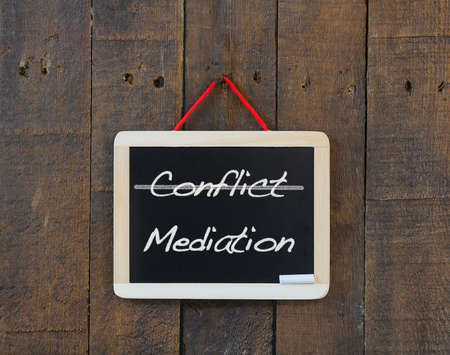mediation: Blackboard old wooden with word conflict and mediation.