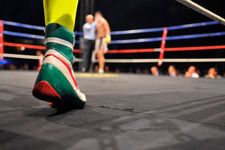 boxing match: View of a ring in a boxing match with boxer feet in the foreground