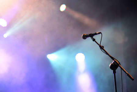 blue spotlight: Microphone with spotlights with colored lights at a rock concert.