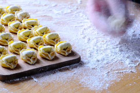tortellini: Preparing homemade tortellini on wooden table in the kitchen. Stock Photo