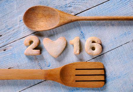 comida: galletas hechas en casa en forma de n�meros de A�o Nuevo de 2016, cuchara de madera y una esp�tula en el cuadro azul. Desde arriba.