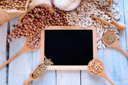 Different types of beans around black framed square on blue wooden table. From above.