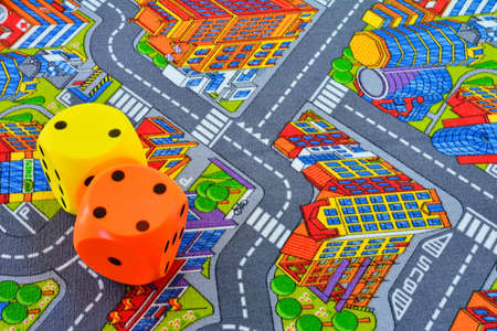 child room: Carpet with painted roads and building in child room. Yellow and orange dice on top.From above.