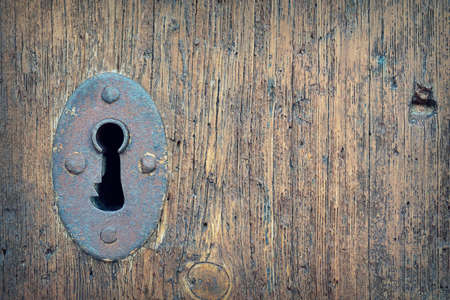 Close-up of old weathered door with rustic keyhole. Stock Photo