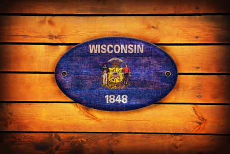wisconsin flag: Wisconsin flag on brown wooden planks.