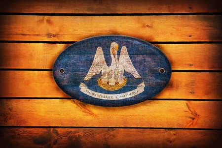 louisiana flag: A Louisiana flag on brown wooden planks.