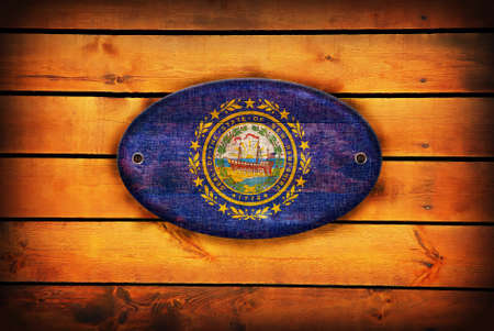 hampshire: A New Hampshire flag on brown wooden planks.