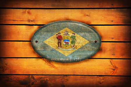 delaware: A Delaware flag on brown wooden planks. Stock Photo