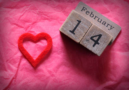 event icon: Wooden calendar with February 14th and red cut heart on pink paper. From above. Stock Photo