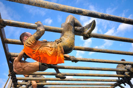 GIJON, SPAIN - JANUARY 31: Farinato Race, extreme obstacle race in January 31, 2016 in Gijon, Spain. People jumping, crawling,passing under a barbed wires or climbing obstacles during extreme obstacle race.
