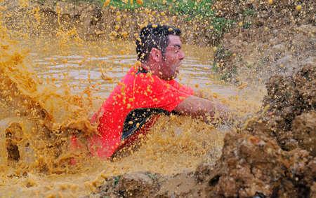 GIJON, ESPAÑA - 31 de enero: Farinato Race, carrera de obstáculos extrema el 31 de enero, 2016, Gijón, España. Salto de la gente, que se arrastra, pasando por debajo de los alambres de púas o subir obstáculos durante la carrera de obstáculos extrema. Editorial