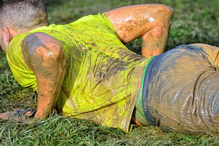wet t shirt: Man doing exercise on sports field. Close-up. Unrecognizable