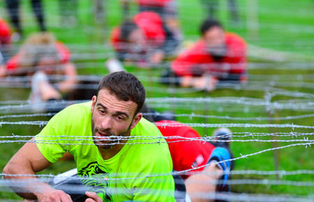 barbed wires: GIJON, SPAIN - JANUARY 31: Farinato Race, extreme obstacle race in January 31, 2016 in Gijon, Spain. People jumping, crawling,passing under a barbed wires or climbing obstacles during extreme obstacle race.