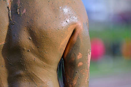 muddy: Close-up of muddy mans back.Unrecognizable Stock Photo