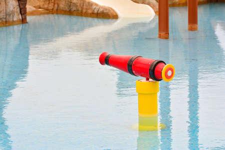 water gun: Red and yellow water gun in swimming pool. Nobody.