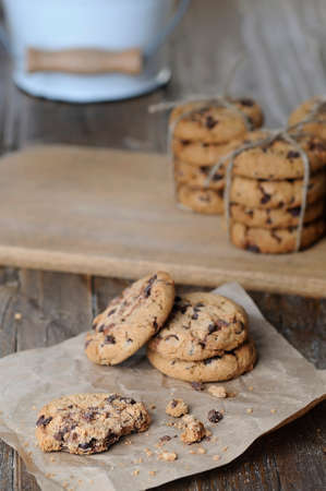 Stacks of homemade chocolate chip cookies on wooden table