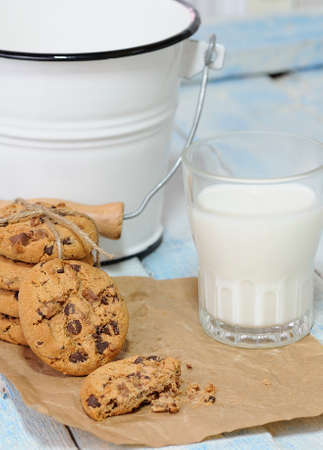 One bitten and stack of chocolate chip cookies with glass of milk on baking paper. Bucket on background. Stock Photo