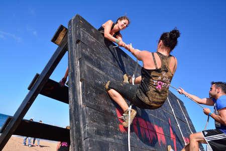 GIJON, SPAIN - SEPTEMBER 19: Storm Race, an extreme obstacle course in September 19, 2015 in Gijon, Spain. Participants in extreme obstacle course jumping a wooden wall.