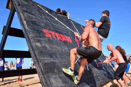 GIJON, SPAIN - SEPTEMBER 19: Storm Race, an extreme obstacle course in September 19, 2015 in Gijon, Spain. Participants in extreme obstacle course jumping a wooden wall. Editorial