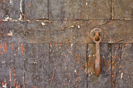 worn out: Close-up of worn out shabby wooden door with rusty metal doorbell