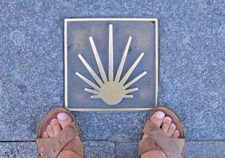 way of st  james: Metal signal in asphalt, Way of St. James in Spain, mans feet in sandals on sidewalk.From above