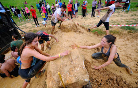 OVIEDO, SPAIN - JUNE 5: Storm Race, extreme obstacle race in June 5, 2016 in Oviedo, Spain. People jumping, crawling,passing under a barbed wires or climbing obstacles during extreme obstacle race. Editorial