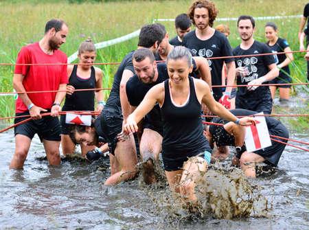 LA FRESNEDA, ESPAÑA - 2 de julio: Gladiador Race, carrera de obstáculos extrema el 2 de julio, 2016, La Fresneda, España. La gente saltando, arrastrándose, pasando por debajo de los alambres de púas durante la carrera de obstáculos extrema.