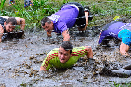 barbed wires: LA FRESNEDA, SPAIN - JULY 2: Gladiator Race, extreme obstacle race in July 2, 2016 in La Fresneda, Spain. People jumping, crawling,passing under a barbed wires during extreme obstacle race.
