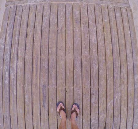 fish eye: Fish eye shot of male feet in flip-flops on wooden planks.above.Copy space.