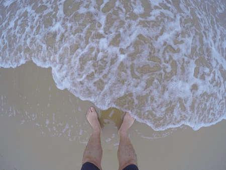 pies masculinos: Fresh sea water touching male feet on sand.Above.Fish eye.