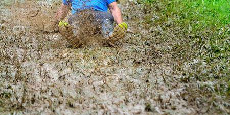 challange: Unrecognizable man sliding the muddy slope making dirty splashes around Stock Photo