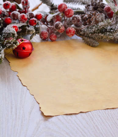faux: Close-up of brown wrapping paper on wooden table with snowed faux fir-tree branch with christmas ball and berries Stock Photo