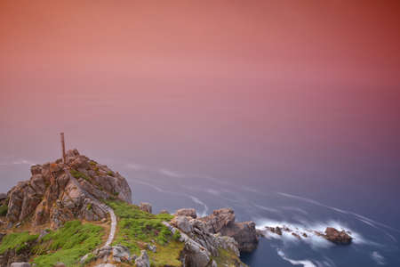 Rocky cliff at sea with pink gradient Stock Photo